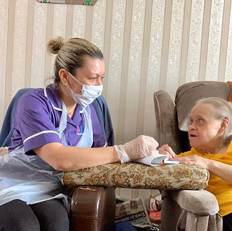 Healthcare worker assisting a female client with writing