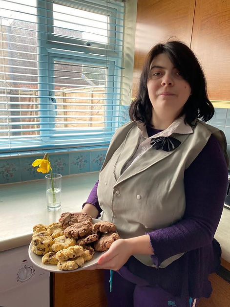 Young woman standing in her kitchen with a plate of baked cookies in her hand