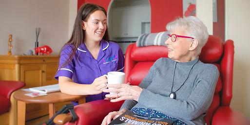 Carer handing an elderly client a cup of tea in her armchair