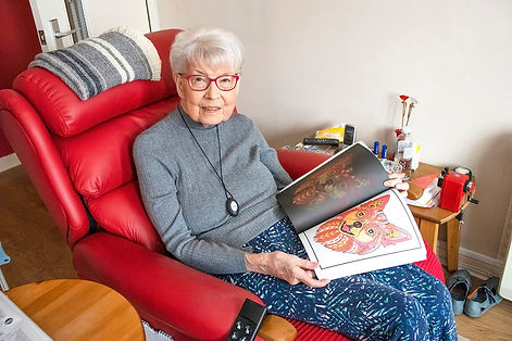 Elderly lady sat in a comfy red chair, showing her artwork colouring skills