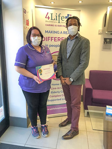 Carer receiving an award for her commitment to care, by the 4Life Healthcare Services' Registered Care Manager
