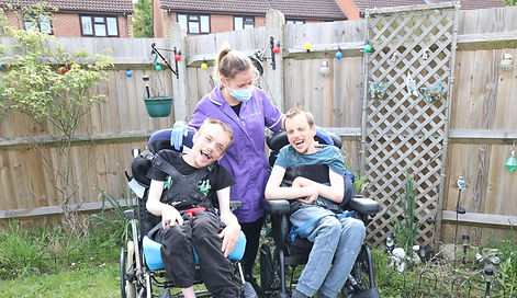 Carer playing with two young boys who are wheelchair bound, in the garden