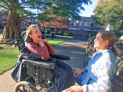 Carer sitting with a young adult who is wheelchair-bound, in Westgate Gardens, Canterbury