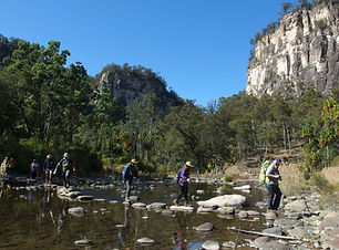 Visitors cross Carnarvon Creek on stepping stones.