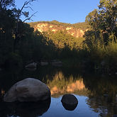 Early morning light on sandstone cliffs is reflected in a still pool in Carnarvon Creek.
