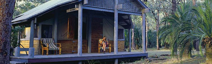 A guest relaxes reading a book on the verandah of her cabin at Carnarvon Gorge Wilderness Lodge.