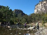Visitors cross Carnarvon Creek via stepping stones while towering cliffs stand sentinel in the background.