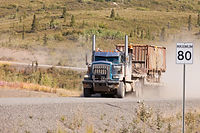industrial-truck-driving-dusty-rural-dirt-road-heavy-duty-articulated-drives-fast-remote-gravel-thro