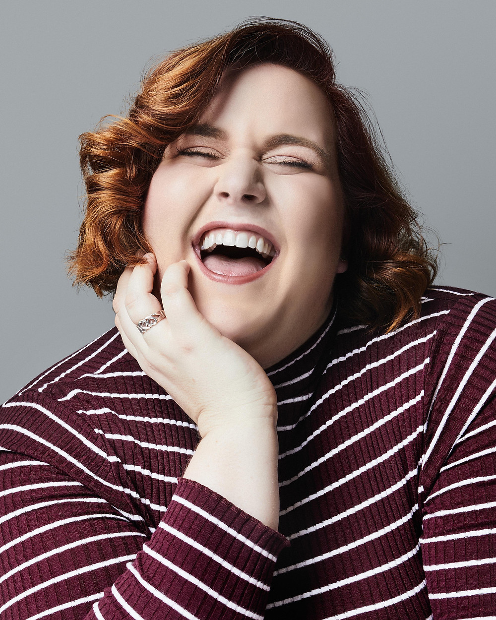 Becca Barrett, a young woman with red hair and fair skin, is wearing a maroon and white striped shirt. Her hand is touching her face, and she is laughing with a wide open smile.