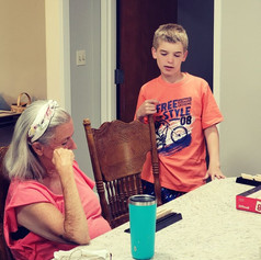 Learning a new game... here our young volunteer Dominic teaches Charlotte how to play Rummikub.