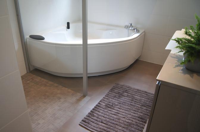 Baignoire d'angle, douche ouverte et meuble vasque