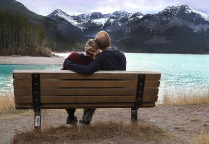 Couple cuddling on a bench in the mountains