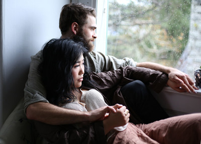 victoria couple looking out window at rain