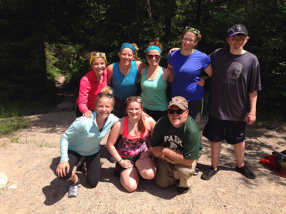 Surrounded by a group of youth and a chaperone after a canoeing trip to the Boundary Waters