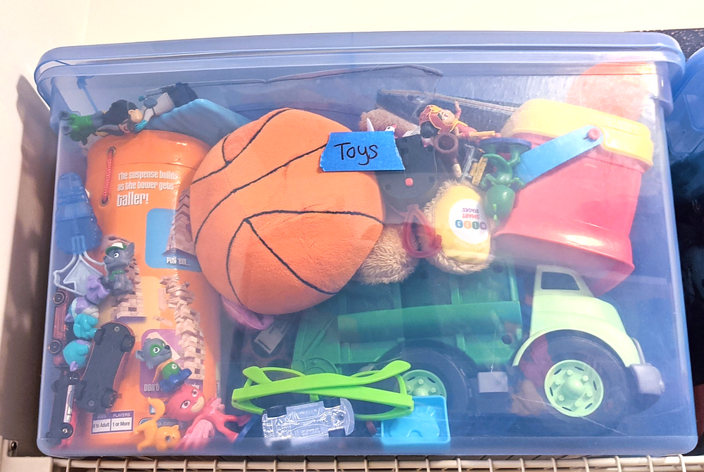 "A clear blue plastic bin is stuffed full of kids toys and sits on a shelf. The bin is labeled ""toys"" with blue painter's tape."