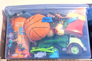 """A clear blue plastic bin is stuffed full of kids toys and sits on a shelf. The bin is labeled """"toys"""" with blue painter's tape."""