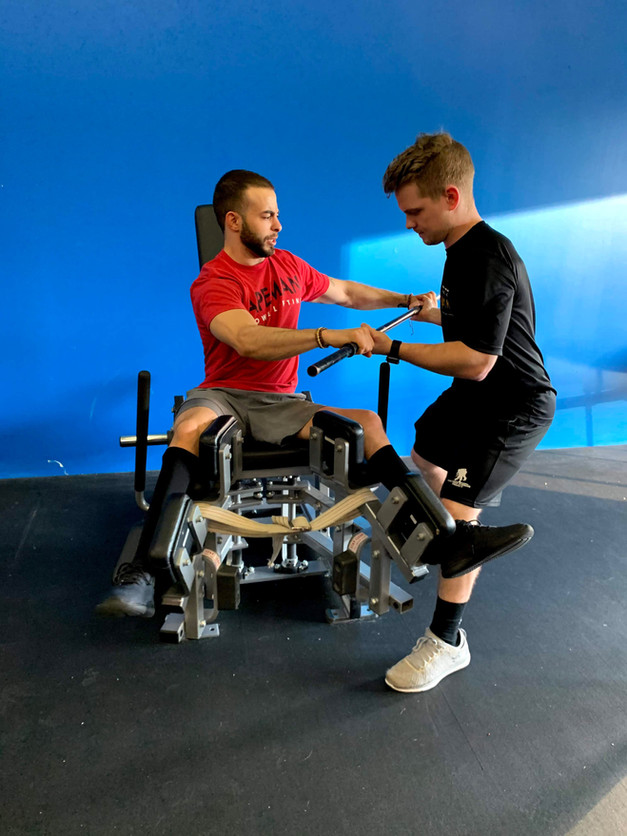 Saleem Baltaji (SCI) works on his core with the abductor and our specialist Nathan Smeester.