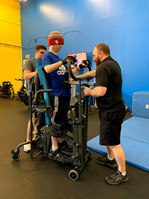 Our specialist Jacob Calhoun works with Nick Dalheim in the standing frame to work on his active standing.
