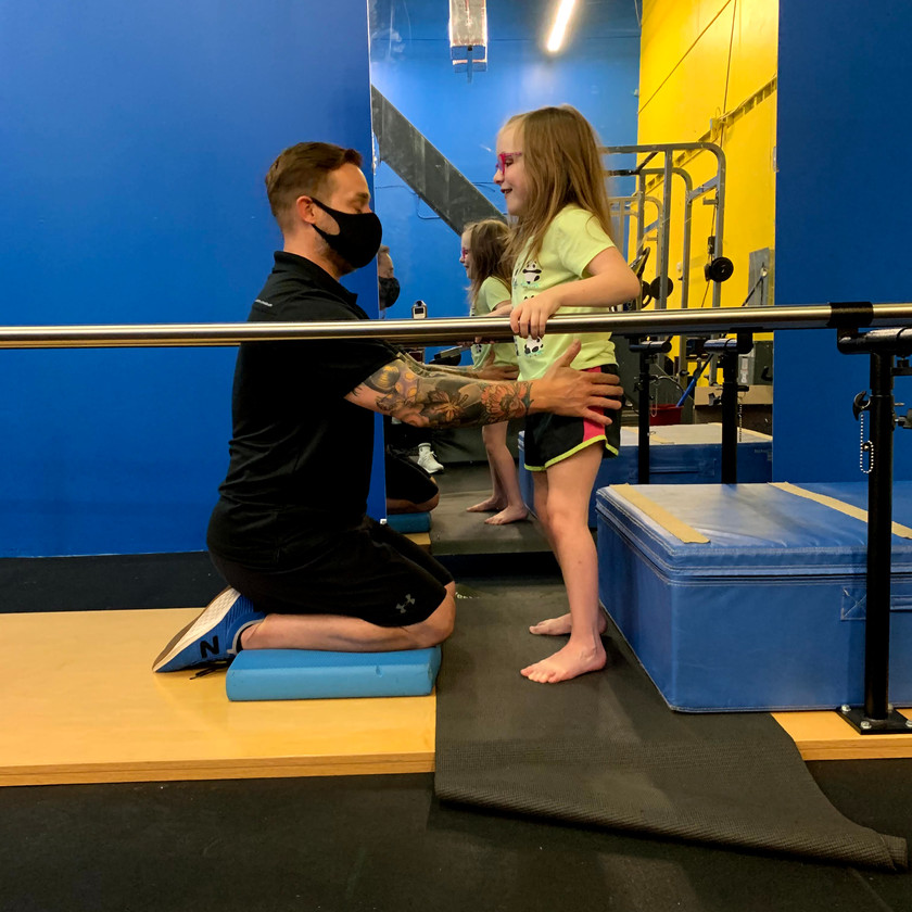 Emma Larsen (CP) is working on her standing balance with our specialist Ross LaBove.