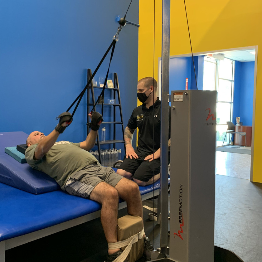 Joao (SCI) is strengthening his posterior chain using the cable weight stack with our specialist Ross.