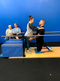 Aubree Ford (CP) is working on her standing balance on the parallel bars with our specialist Ross LaBove.