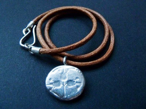 Silver pomegranate coin on leather cord