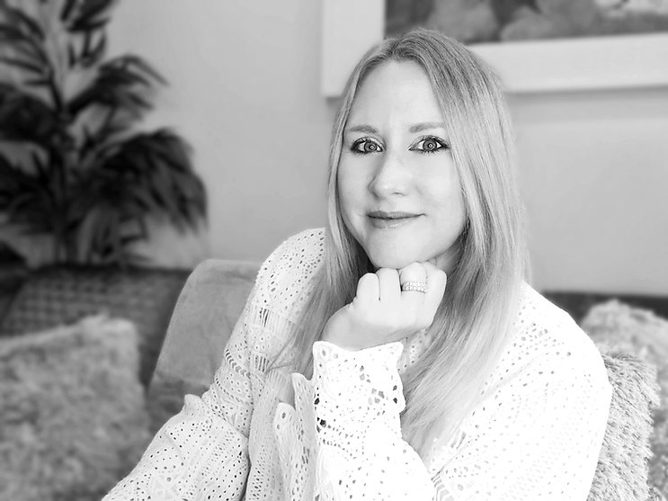 Black and white photo of Liz Hamlet, founder of Spark Succeed. Liz is wearing a white top & smiling