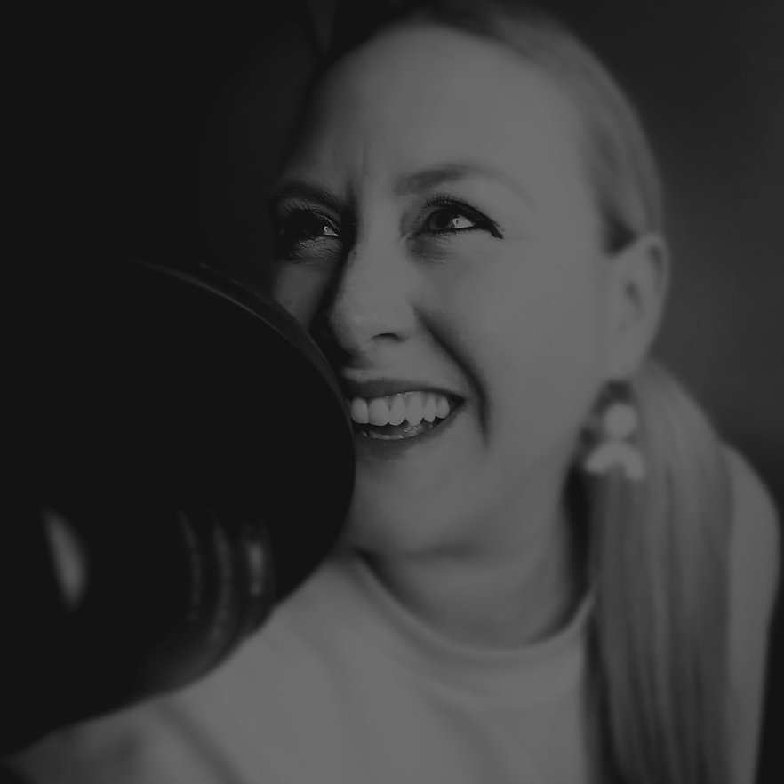 Black and white photo of Liz Hamlet smiling with podcast microphone