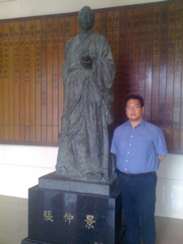 Dr. Tan-Gatue with a statue of Zhang Zhongjing, ancient Chinese Medicine and Acupuncture legend.