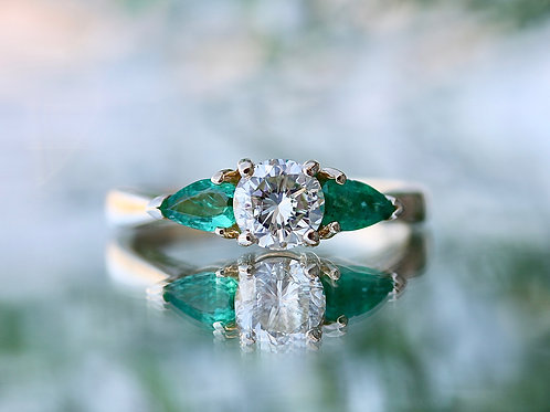 ROUND ENGAGEMENT RING WITH EMERALD SIDE STONES