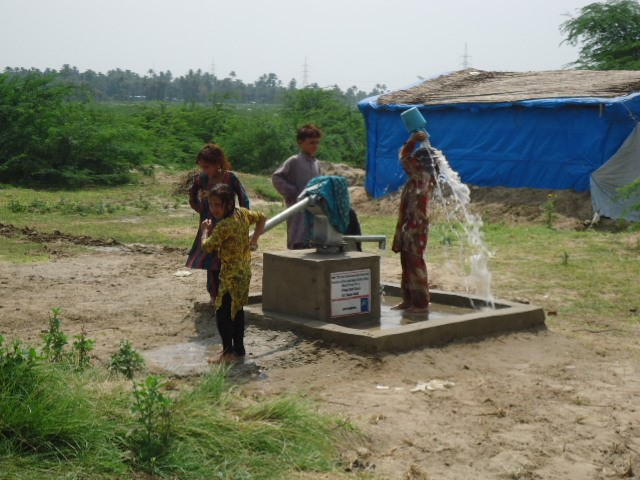 Children using new handpump to bathe