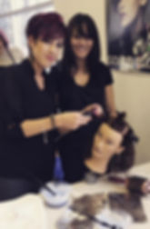 Instructor Mindy helps student color hair on mannequin in beauty school