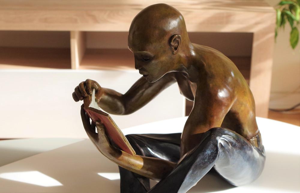 Sculpture bronze d'un homme assis tenant un livre ouvert. Il est assis en tailleur, vêtu d'un jean bleu, torse nu, il lit un livre, tranquille..