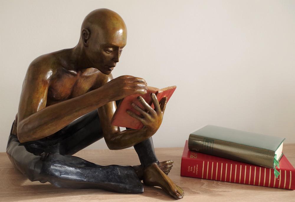 Un homme qui lit, assis, torse nu, jean bleu