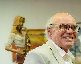 Photo Rémi Coudrain en exposition devant sa sculpture saxophoniste