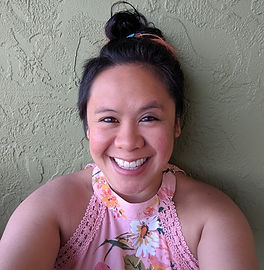 Kristen is a Chinese and Filipina woman. She has her hair in a bun on top of her head and she wears a light pink floral halter top and a big, bright smile.