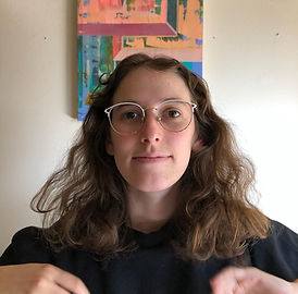 Sasha has light skin and light brown, wavy hair. She is wearing white, wire-framed horn-rimmed glasses and a slight smile.