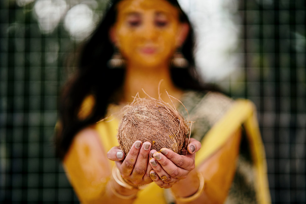 Auckland Indian wedding bride's haldi night as she holds a coconut during the ceremony with the bride in the background out of focus.