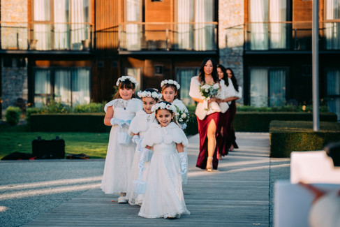 Flower girls and the bridesmaids in a line walking down the aisle.