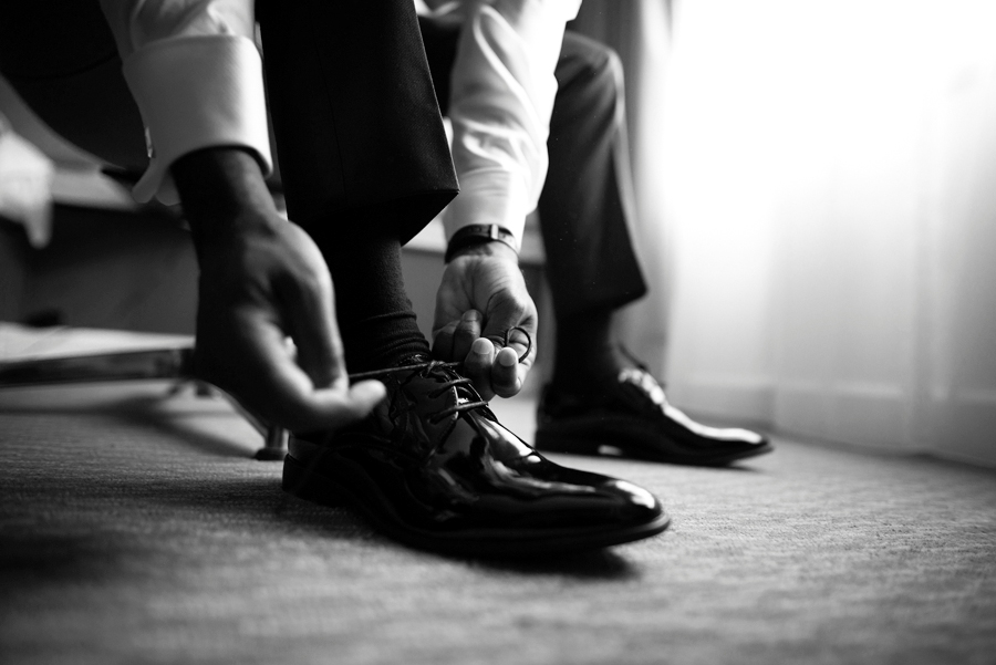Groom wearing his shoes during the groom prep