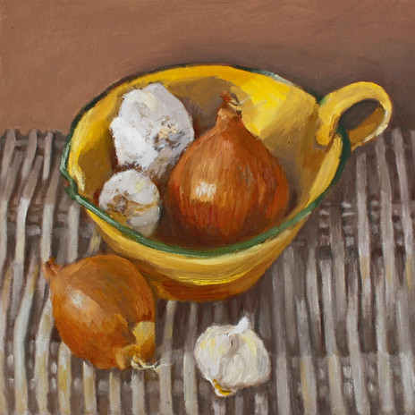 Onions in yellow bowl on rush mat