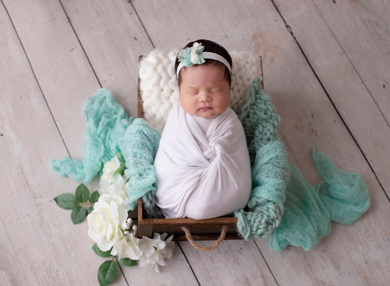 beautiful newborn girl in box prop