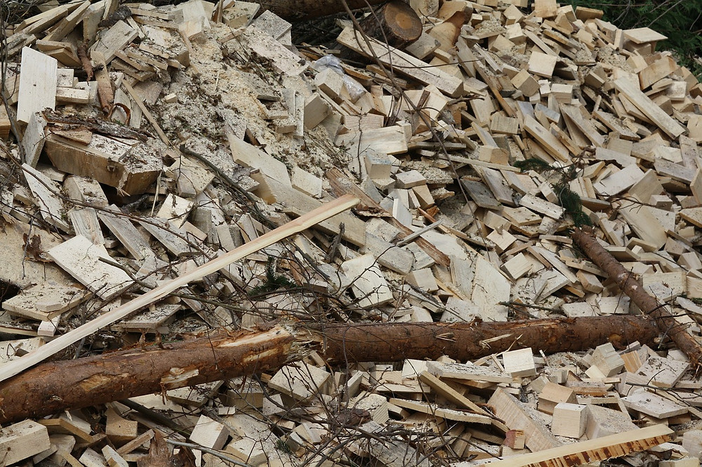 Image shows a pile of wood biomass that includes tree branches and construction material.
