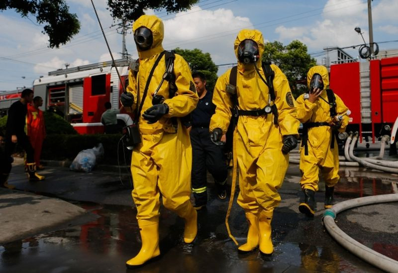 Firemen in protective suits walk near the site of an ammonia leak at a cold storage unit in Shanghai.