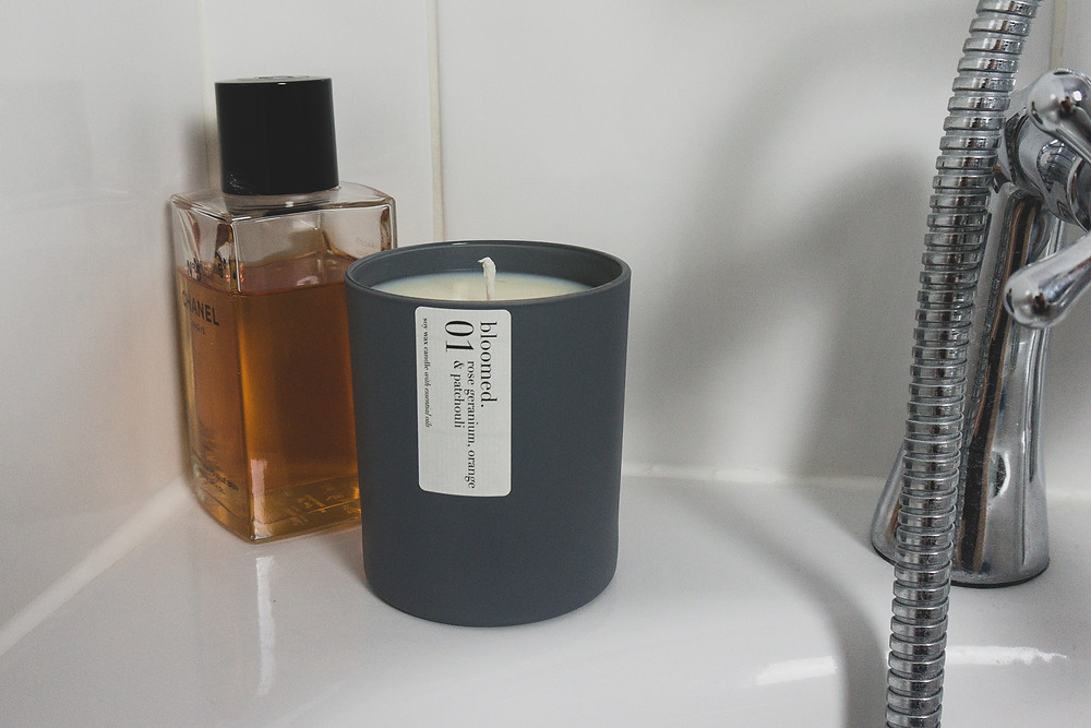 A matte grey soy wax candle on the side of the bath next to a bottle of Chanel bath oil, in front of a white tiled background