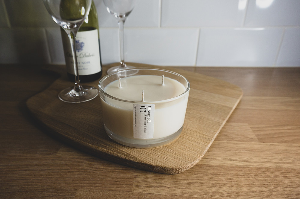 large three wick candle with a bottle of wine and wine glasses