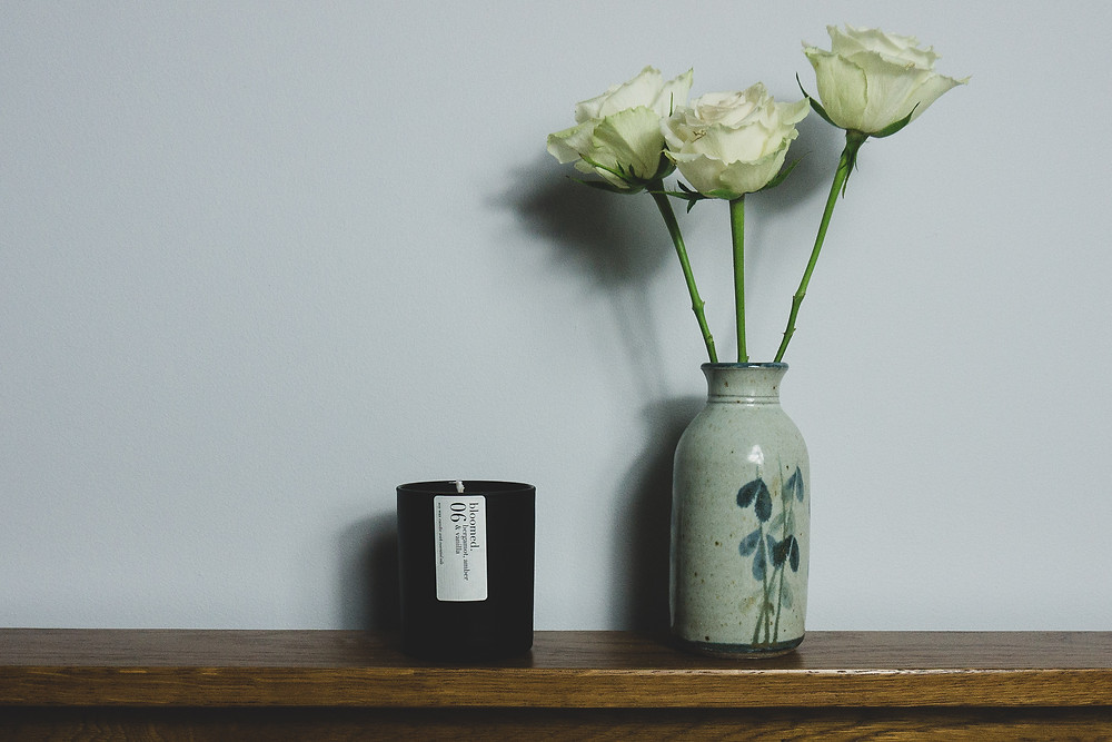 A black matte soy wax candle on a wooden surface, next to a small vase of white roses in front of a plain wall