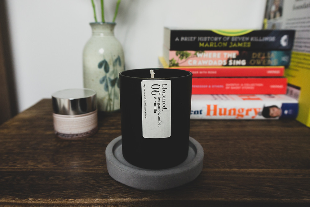 A black matt soy wax candle on a Jesmonite tray sits on a wooden table in front of a small vase of flowers, face cream and a pile of books.