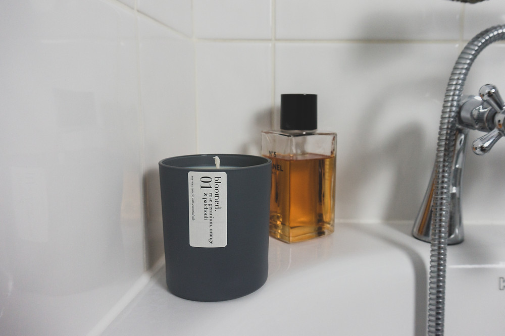 a candle sits by the bath with luxury bath oil