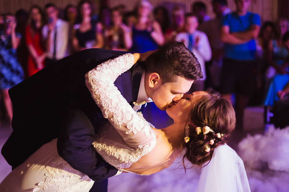 Groom kisses bride while bending over during their first dance.jpg
